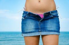 La dame sexy sur la plage déshabille sa jupe avec la tirette ouverte Photographie stock libre de droits