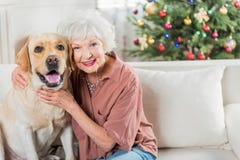 La dame supérieure gaie apprécie le temps avec son animal familier Images stock