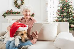 La dame supérieure joyeuse se repose avec son animal familier Photographie stock
