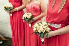 La damigella d'onore lo stessi si è vestita con i mazzi delle rose e dell'altro flo Fotografie Stock Libere da Diritti