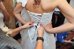 La damigella d'onore sta aiutando la sposa che lega l'arco sopra Fotografia Stock Libera da Diritti