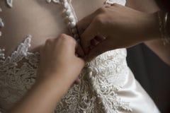 La damigella d'onore sta merlettando il vestito da sposa bianco per la sposa fotografia stock
