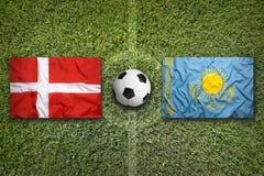 La Danimarca contro Bandiere del Kazakistan sul campo di calcio Immagine Stock