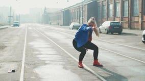 La danse blonde de femme exécute la danse moderne de hip-hop posant, style libre dans la rue, urbaine longueur des actions 4k banque de vidéos
