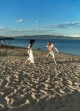 La danse d'homme et de femme, couplent heureux des vacances Couples dans l'amour fonctionnant sur la plage, bord de la mer Couple Image stock
