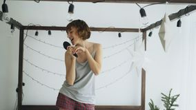 La danse gaie attrayante de femme sur le lit et le chant avec le peigne aiment le microphone à la maison Photographie stock