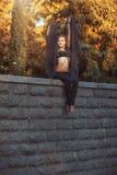 La danseuse de fille dans des vêtements noirs s'assied sur un mur en pierre Photo libre de droits