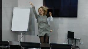 La danza de los compañeros de trabajo o se divierte en oficina Las mujeres de negocios femeninas jovenes celebran éxito Buenos as metrajes