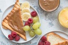 La data del cioccolato della nocciola ha sparso il burro di dado ed il pane tostato del pane sul piatto bianco Diffusione assorti fotografie stock libere da diritti