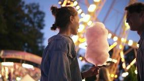 La datación joven de los pares, reunión en el parque de atracciones, varón trae un caramelo de algodón a su novia kissing Brillo  almacen de metraje de vídeo