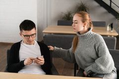 La datazione dell'uomo dell'imbroglione sulla linea con uno Smart Phone e un'amica sta spiando la seduta su un sofà nel caffè fotografia stock