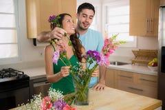 La datazione della donna e dell'uomo allegro ha messo i fiori in un vaso a casa nella cucina Fotografia Stock Libera da Diritti