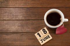 La date civile avec la tasse de café et le coeur forment sur la table Image stock