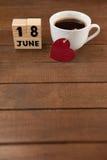 La date civile et la tasse de café avec le coeur forment sur la table Images libres de droits