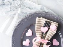 La date romantique de dîner plaque des verres de champagne de coeurs sur le gris Photos stock