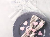 La date romantique de dîner plaque des verres de champagne de coeurs sur le gris Photo stock
