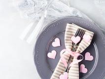 La date romantique de dîner plaque des verres de champagne de coeurs sur le gris Images stock