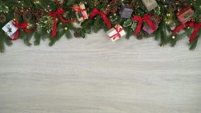 La decoración de arriba de colocación remata el marco en fondo de madera ligero con los conos del pino, regalos, cintas rojas del metrajes