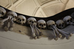La decoración de cráneos y de huesos humanos en un osario del gótico de la iglesia del cementerio de todos los santos en Kutna-Ho Foto de archivo