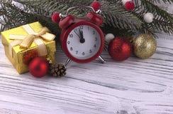 La decoración de la Navidad con el abeto natural del cono rojo del despertador de la caja de regalo ramifica bola de oro en el fo Imagen de archivo libre de regalías