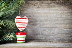 La decoración de la Navidad con el abeto ramifica en el fondo de madera Imagen de archivo