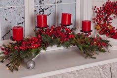 La decoración de la Navidad con las velas rojas, las bayas, las luces de la guirnalda y el pino ramifican Fotografía de archivo libre de regalías
