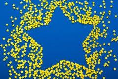 La decoración de la Navidad del confeti de oro protagoniza contra backg azul Fotografía de archivo