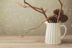 La decoración de la tabla de la Navidad con el jarro y el invierno ramifica Imagenes de archivo