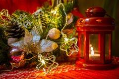 La decoración de la Navidad con la vela y la guirnalda se enciende en fondo rústico rojo Fotografía de archivo