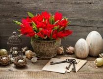 La decoración de Pascua con la jaula, los huevos y el tulipán florece Imagen de archivo
