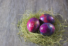 La decoración de Pascua eggs en un heno en un fondo gris Fotografía de archivo libre de regalías