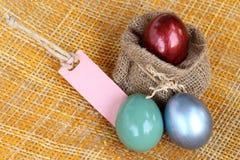 La decoración de Pascua, los huevos coloridos y el papel en blanco marcan con etiqueta Imagen de archivo