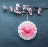 La decoración de la primavera con la ramita artificial del flor de la primavera y el rosa van de fiesta la fan de papel fotografía de archivo