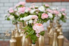 La decoración de Weddind florece en botellas golded y del brozne foto de archivo libre de regalías