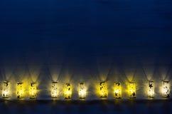 La decoración del Año Nuevo, luces quema en fondo azul de madera del añil Imagen de archivo