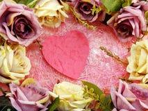 La decoración del símbolo del corazón con las rosas artificiales florece las aplicaciones para el día de tarjetas del día de San  Imagenes de archivo