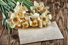 La decoración del vintage con los narcisos florece en el viejo tablero de madera con el espacio de la copia Imagenes de archivo