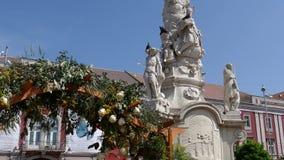 La decoración floral con dos estatuas de madera se vistió en un traje popular hecho de flores metrajes