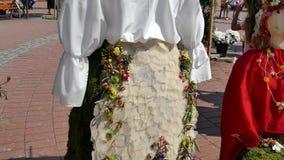 La decoración floral con dos estatuas de madera se vistió en un traje popular hecho de flores almacen de video