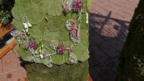 La decoración floral con dos estatuas de madera se vistió en un traje popular hecho de flores almacen de metraje de vídeo