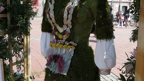 La decoración floral con una estatua de madera se vistió en un traje popular hecho de flores almacen de video