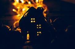 La decoración hermosa de la Navidad con las mandarinas y una casa del juguete en la noche encienden las guirnaldas Todavía de la  Fotografía de archivo