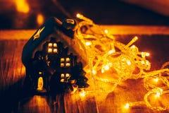 La decoración hermosa de la Navidad con las mandarinas y una casa del juguete en la noche encienden las guirnaldas Todavía de la  Foto de archivo libre de regalías
