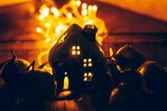 La decoración hermosa de la Navidad con las mandarinas y una casa del juguete en la noche encienden las guirnaldas Todavía de la  Fotografía de archivo libre de regalías