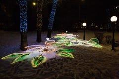 La decorazione delle luci di Natale su neve ha illuminato la via nelle feste di notte dell'inverno Fotografie Stock