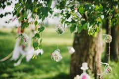 La decorazione di nozze stona con i fiori che appendono sulle corde sui rami di una betulla Immagini Stock