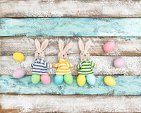 La decorazione di Pasqua eggs il fondo di legno dei coniglietti divertenti Fotografia Stock
