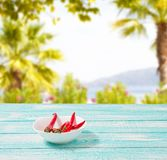 La decorazione di peperoncino rovente sul blu wodden il bordo sul fondo vago della spiaggia Insieme, spazio della copia, falso su fotografia stock