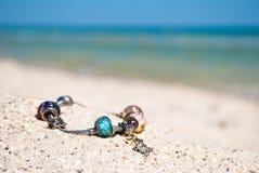 La decorazione femminile del braccialetto si trova sulla sabbia su un fondo del mare e del cielo blu blu immagine stock libera da diritti