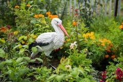 La decorazione per il giardino floreale, la cicogna dell'uccello sta fra i fiori Immagini Stock